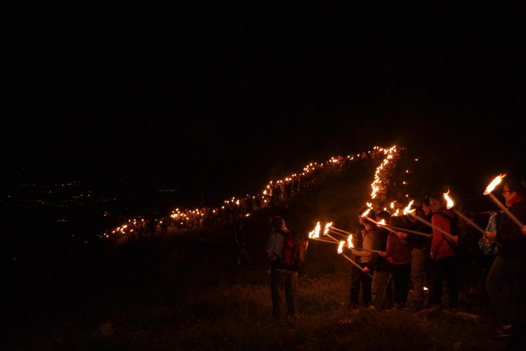la suggestiva processione delle torce che illumina la notte nelle montagne